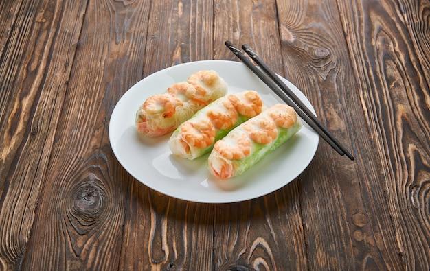 Rouleaux de printemps de la cuisine asiatique aux crevettes sur un fond en bois foncé. rouleaux de printemps en papier de riz avec des baguettes. espace pour le texte