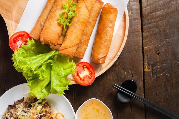 Rouleaux de printemps frits croustillants avec sauce aux prunes et salade, tranches de citron sur la table en bois