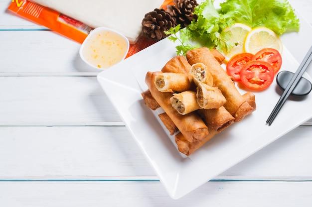 Rouleaux de printemps frits croustillants avec sauce aux prunes et salade, tranches de citron