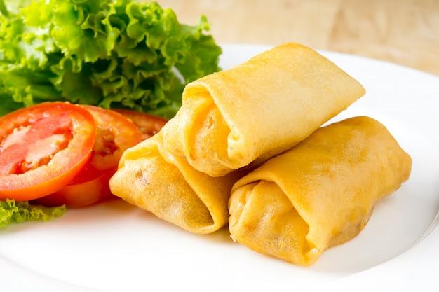 Rouleaux de printemps frits avec des légumes sur un plat blanc