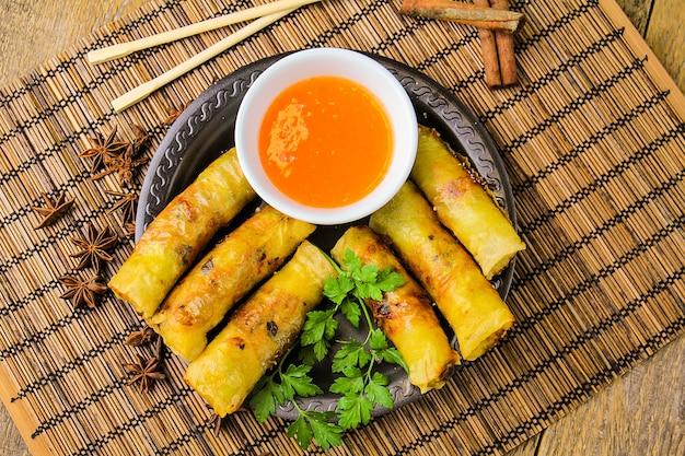 Rouleaux de printemps avec sauce sucrée, vue de dessus, bâtonnets chinois