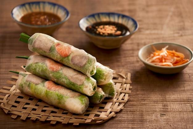 Rouleaux de printemps vietnamiens - feuille de riz, laitue, salade, vermicelles, nouilles, crevettes, sauce de poisson, chili doux, soja, citron, veletables. espace de copie. cuisine asiatique et vietnamienne. cuisine nationale traditionnelle
