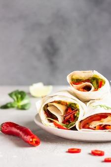 Rouleaux de sandwichs avec salade de légumes servis avec un mélange de salade, citron vert et piment sur une plaque