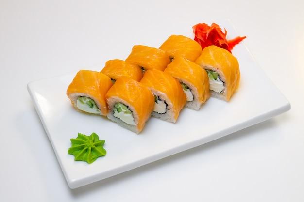 Rouleaux de saumon et concombre, fromage et wasabi sur une plaque blanche