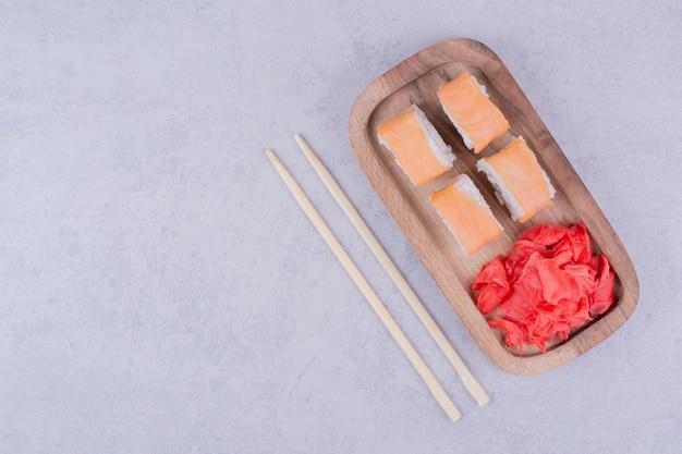 Rouleaux de saumon dans une assiette en bois avec du gingembre mariné.