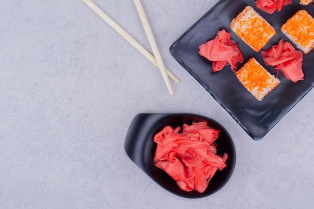 Rouleaux de saumon et gingembre mariné rouge dans un plat noir.