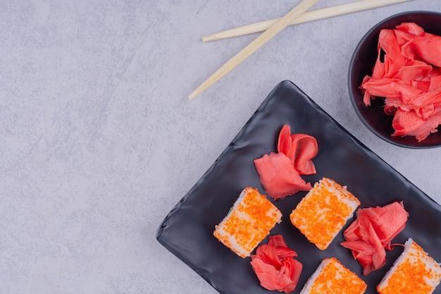 Rouleaux de saumon de philadelphie au gingembre rouge sur un plateau en céramique