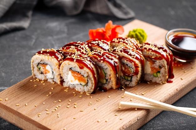 Rouleaux de sushi américains avec unagi et saumon sur la planche de bois