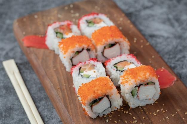 Rouleaux de sushi au caviar jaune et rouge sur une planche de bois.