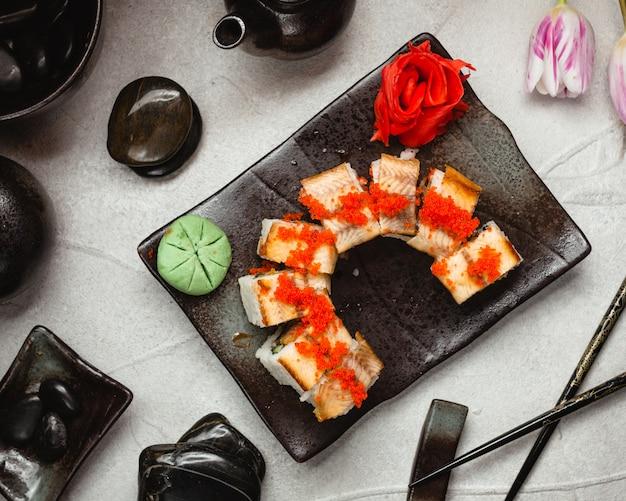 Rouleaux de sushi au paprika sur un tableau en pierre noire avec du gingembre rouge et du wasabi.