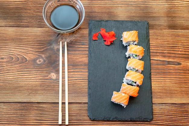 Rouleaux de sushi au poisson avec saumon, gingembre, sauce soja et baguettes sur une planche à découper noire sur fond rustique en bois avec espace de copie. fruits de mer, service alimentaire du concept de restaurant se bouchent.