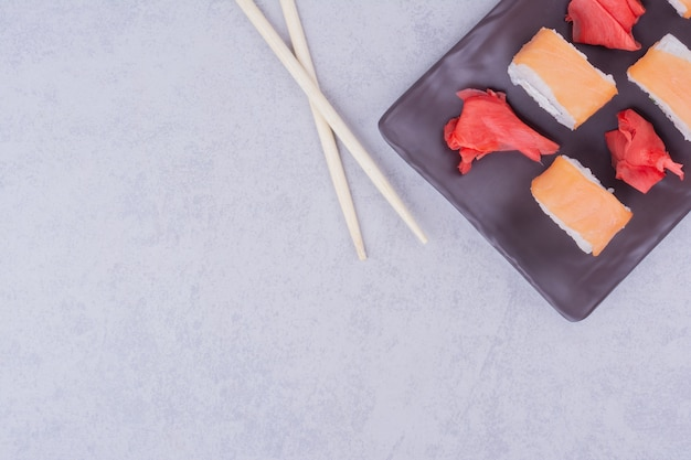 Rouleaux de sushi au saumon dans des assiettes en céramique noire