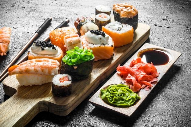Rouleaux de sushi au saumon et légumes sur une planche à découper avec sauce et baguettes. sur fond rustique noir