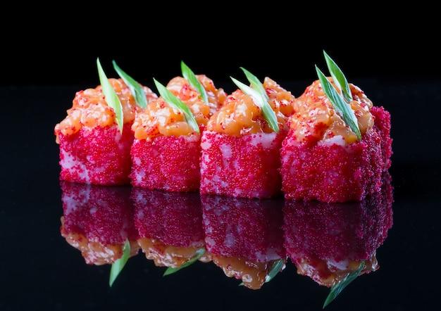 Rouleaux de sushi au saumon, sauce épicée sur fond noir.
