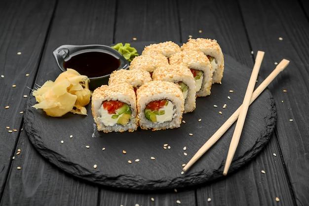 Rouleaux de sushi au sésame avec avocat, saumon et fromage à la crème sur fond noir