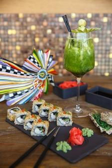 Rouleaux de sushi au sésame servis avec du gingembre et du wasabi servis avec cocktail de kiwi