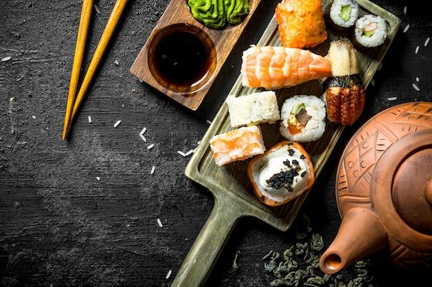 Rouleaux de sushi aux crevettes, saumon et légumes sur une planche à découper avec des baguettes. sur fond rustique noir