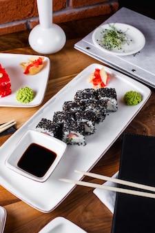 Rouleaux de sushi aux graines de sésame servis avec sauce soja, gingembre et wasabi