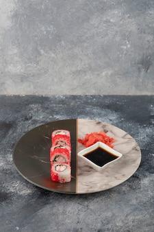 Rouleaux de sushi californiens, gingembre et sauce soja sur plaque de marbre