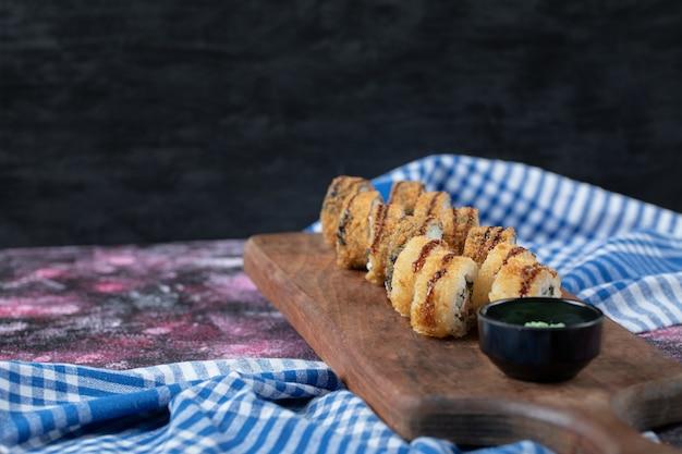 Rouleaux de sushi chauds frits sur une planche de bois avec sauce wasabi.