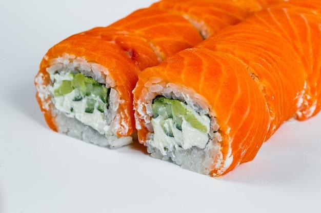 Rouleaux de sushi classiques avec du saumon frais et du fromage à la crème. cuisine traditionnelle japonaise