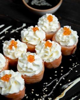 Rouleaux de sushi à la crème et au caviar rouge servis avec du gingembre et du wasabi