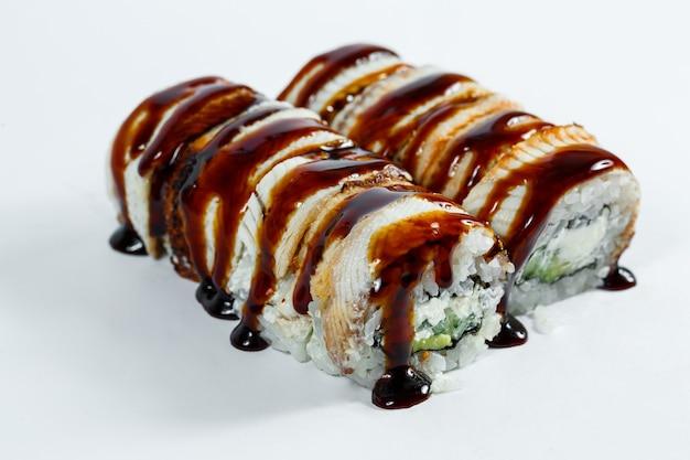 Rouleaux De Sushi De Cuisine Japonaise Avec Anguille Et Fromage à La Crème Garnis De Sauce Unagi Photo Premium