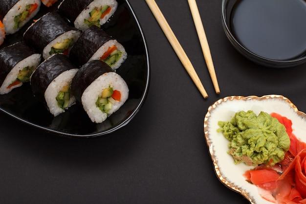 Rouleaux de sushi dans des feuilles d'algues nori avec avocat et poisson rouge sur plaque en céramique. assiette avec gingembre mariné rouge et wasabi. bol avec sauce soja et bâtonnets en bois. vue de dessus.