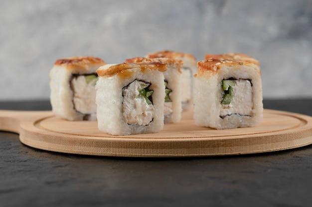 Rouleaux de sushi dragon savoureux avec anguille sur planche de bois