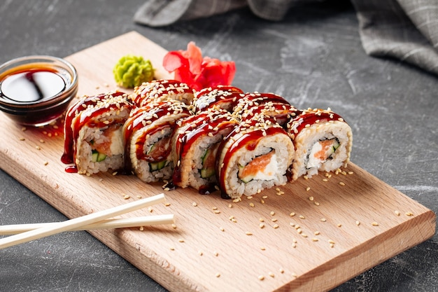 Rouleaux de sushi du canada américain avec unagi et saumon sur la planche de bois