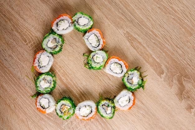Des rouleaux de sushi étaient posés sur la table en forme de cœur. ensemble de vacances pour la saint-valentin. vue de dessus.