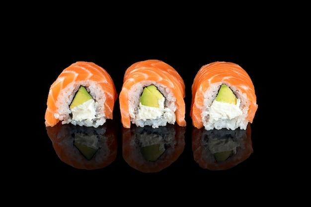 Rouleaux de sushi faits de saumon cru frais, de fromage à la crème et d'avocat isolé sur fond noir avec des reflets