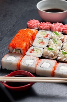 Rouleaux de sushi sur un fond de pierre sombre avec des bâtons de bambou et de la sauce soja