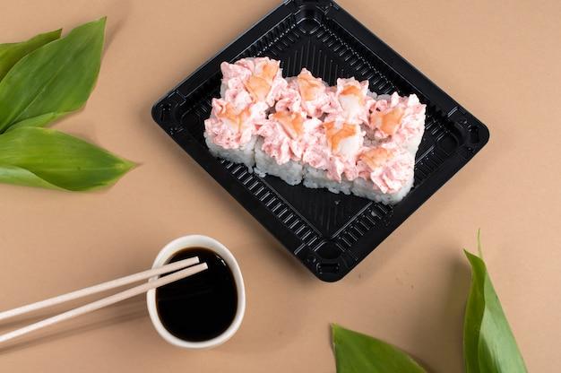 Rouleaux de sushi garnis de fromage à la crème rose et de crevettes. rouleaux de sushi dans des contenants en plastique noir. livraison de plats asiatiques à domicile.