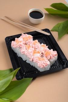 Rouleaux de sushi garnis de fromage à la crème rose et de crevettes. rouleaux de sushi dans des contenants en plastique noir avec sauce soja et baguettes