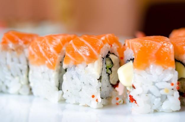 Rouleaux, sushi et gingembre sur une assiette blanche et une surface légère.