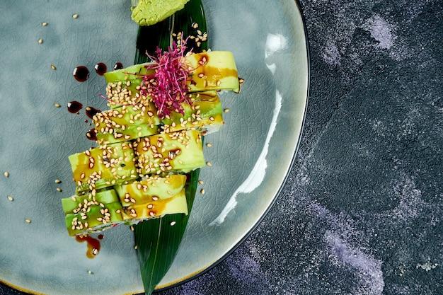 Rouleaux de sushi japonais à l'anguille et à l'avocat dans une assiette bleue sur fond noir. rouler le dragon vert