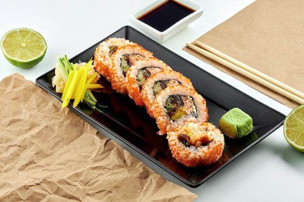 Rouleaux de sushi japonais classiques avec garniture. uramaki à l'avocat, caviar tobiko et saumon tempura, servi dans une assiette noire