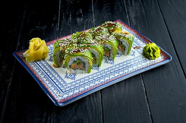 Rouleaux de sushi japonais frais à l'avocat, sauce unagi et thon, servis dans une assiette bleue sur fond sombre.