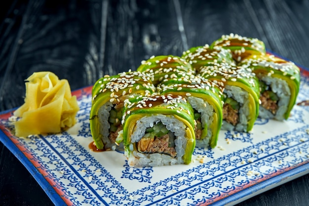 Rouleaux de sushi japonais frais avec avocat, sauce unagi et thon, servis dans une assiette bleue sur une surface sombre. cuisine japonaise