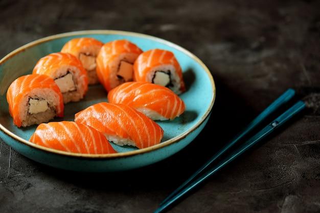 Rouleaux de sushi maison philadelphia et nigiri dans une assiette bleue sur une surface noire.
