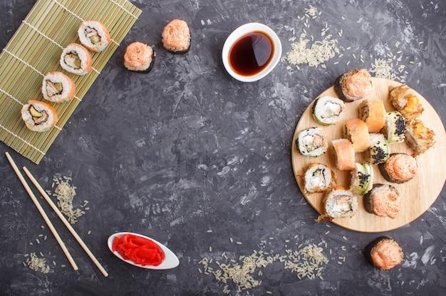 Rouleaux de sushi maki japonais assortis de baguettes, gingembre, sauce soja, riz sur fond de béton noir, vue de dessus.