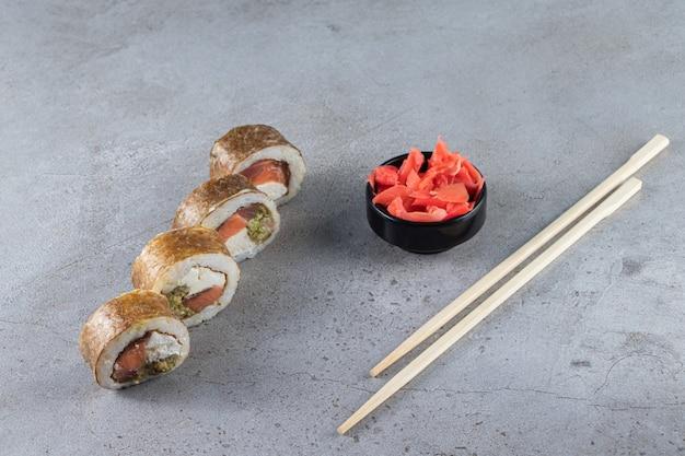 Rouleaux de sushi, sauce soja, wasabi et gingembre mariné sur fond de pierre.