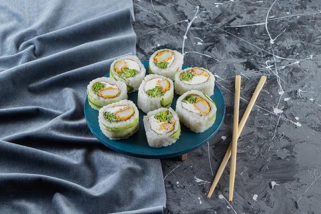 Rouleaux de sushi, sauce soja, wasabi et gingembre mariné sur table en pierre.