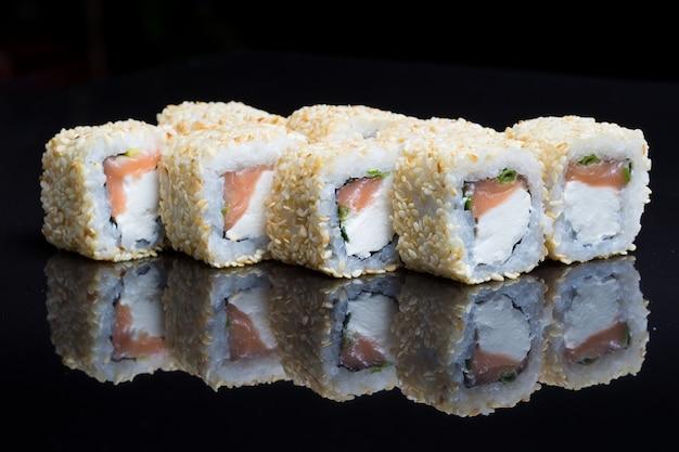 Les rouleaux de sushi secouent le chizu au sésame sur fond noir.