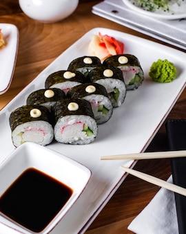 Rouleaux de sushi servis avec sauce soja, gingembre et wasabi