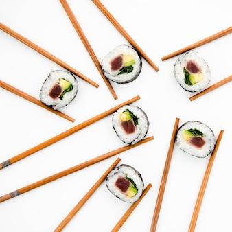 Rouleaux de sushi tenus dans des baguettes sur un fond blanc