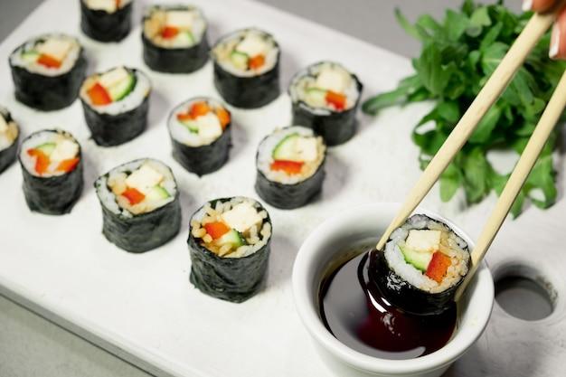 Rouleaux de sushi végétaliens au quinoa, légumes et sauce soja sur une assiette blanche, fond clair. concept d'aliments sains végétaliens. vue de dessus, espace de copie