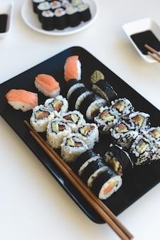 Rouleaux de sushis faits maison sur plaque noire