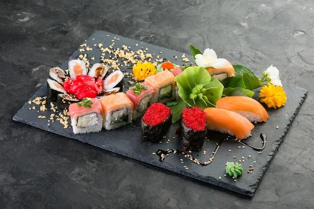 Rouleaux et sushis sur un fond noir d'ardoise, cuisine japonaise
